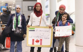 Canadians await the first plane's arrival of Syrian refugees at Toronto's Pearson International Airport in December