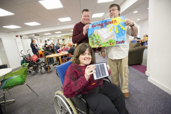 Disability Stockport and Ridgeway (front) and back L-R Stephen Kane and Kieran McMahon. Pictured with a solar power themed poster made by group members made. (photograph: Chris Bull )