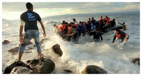 IsraAID nurse Malek Abu-Gharara helps bring Syrian refugees ashore at Lesvos, Greece