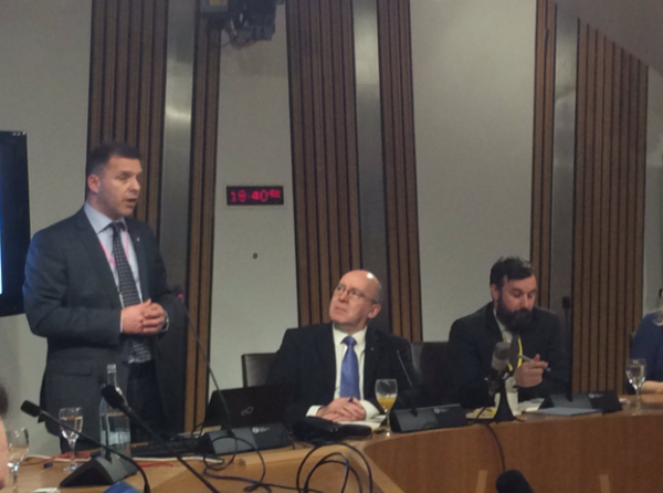 Kari Huhtala speaking at the Scottish Parliament with Willie Coffey MSP and James Wright and James Proctor, strategic relations officer at Co-operatives UK