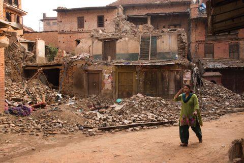 A survivor walks past rubble in quake-damaged Bhaktapur