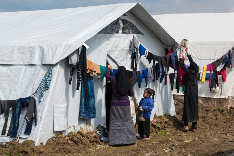 Two women try to dry their clothes after heavy rain in the refugee camp of Idomeni, Greece