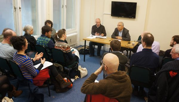 John Hunt and Alan Semo (l-r on desk at front) lead a discussion into the co-ops and communities of Rojava, northern Syria