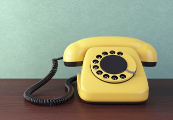 Yellow telephone on wooden table